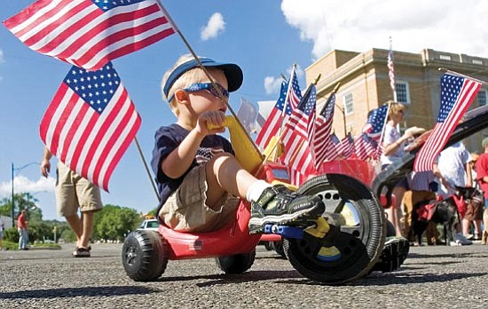 Matt Hinshaw/<br>The Daily Courier<br>Beau Brchan, 3, rides his big wheel down Cortez St. during the 68th Annual Prescott Kiwanis Club Kiddie Parade Friday morning in Prescott.