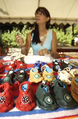Les Stukenberg/The Daily Courier<p> Sharon Campbell talks to a client as she sews beads onto an infant's moccasin at the 2005 Prescott Indian Art Market at the Sharlot Hall Museum.