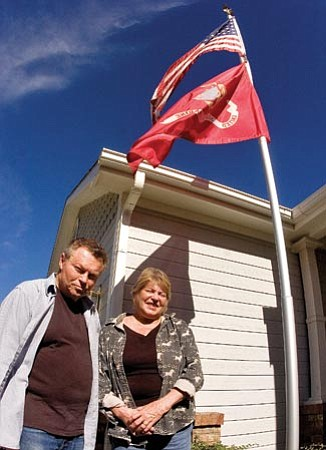 Matt Hinshaw/The Daily Courier<p> Dan and Donita McLellan stand in front of their Victorian Estates home in Prescott Valley Wednesday afternoon. The McLellans recently got into a dispute with their homeowners association over placement of their military service flag.