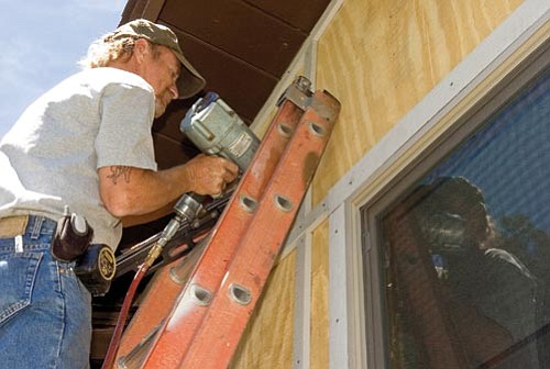 Matt Hinshaw/The Daily Courier<p> Rick Dancey, a carpenter with DeCarol Co. General Contracting, works on putting siding onto a home in Prescott Thursday afternoon.