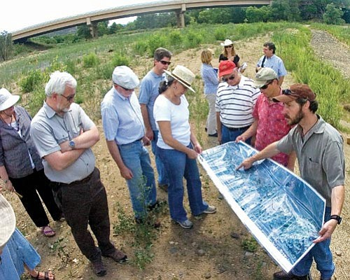 Matt Hinshaw/The Daily Courier Prescott Creeks Preservation Association Executive Director Michael Byrd, right, shows commissioners and staff from the Arizona Water Protection Fund, among others, an updated aerial map of the Watson Woods Restoration project Tuesday in Prescott.