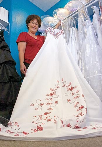 Matt Hinshaw/The Daily Courier<p> Shari Curry Camp,  owner of Elegant Brides in Prescott Valley, displays one of her many wedding dresses Wednesday morning. Camp has owned a bridal shop for the past 11 years.