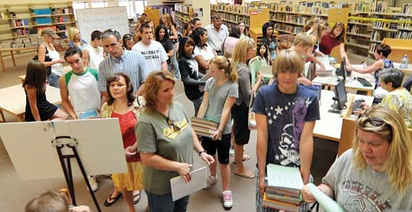 Les Stukenberg/The Daily Courier<br> Parents and freshman students wait to pay fees and pick up their text books at the Bradshaw Mountain High School registration on Thursday.