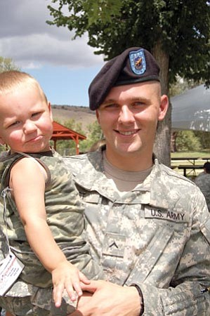 Ken Hedler/The Daily Courier<br> Jonathan Ohst of the Arizona National Guard unit in Prescott holds his 1-year-old son, Caleb, during the second annual Operation Welcome Home event Sunday.