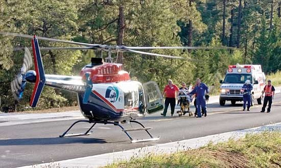 Matt Hinshaw/<br>The Daily Courier<br>Life Line and Guardian Air paramedics transport a stabbing victim to a Guardian Air helicopter on Copper Basin Rd near West Timber Ridge Rd late Tuesday afternoon in Prescott. The unidentified man was reportedly stabbed repeatedly by a family member.
