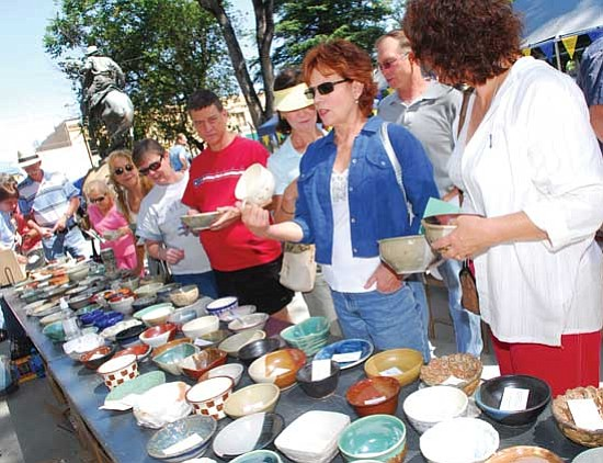 Les Stukenberg/<br>The Daily Courier<br>Patrons look for their favorite bowl for soup and a good cause at last year's Empty Bowls event on the Yavapai County Courthouse Plaza.