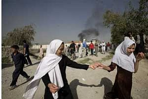 Afghan girls head for school hand-in-hand as black smoke billows from the site of a car bomb blast outside the entrance to the military airport in Kabul, Afghanistan, Tuesday, Sept. 8, 2009. The Taliban claimed responsibility for the blast. <i>(AP Photo/Farzana Wahidy)</i>