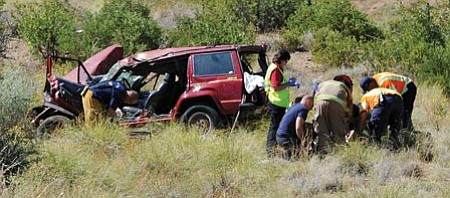 Les Stukenberg/The Daily Courier<br> Firefighters from Mayer and Central Yavapai along with LifeLine Ambulance personnel treat the victim of a single-vehicle rollover accident near Mayer on Monday morning.