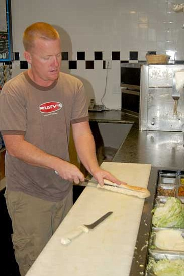 Jason Soifer/<br>The Daily Courier<br>Rusty's co-owner Rusty Mosher, above, makes a sandwich in his Prescott Valley sub shop Wednesday.