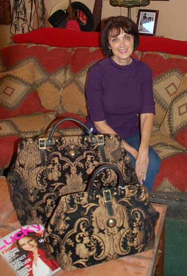 "Paula Rhoden/<br>The Daily Courier<br>Kathy Tarantino displays the carpetbags she and her husband Jerry make at their Chino Valley residence. Lucky, a fashion magazine, spotlights the Victorian ""Mary Poppins-style"" bags in its November issue."