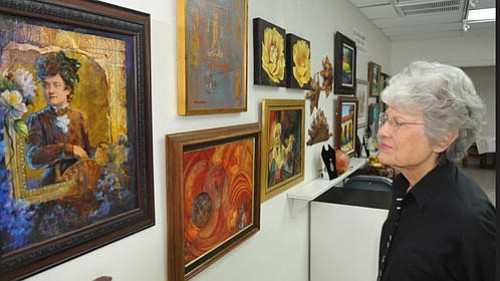 Les Stukenberg/<br>The Daily Courier<br> Wanda Lyman looks at some of the art work that will be auctioned at the annual Mountain Artist Guild Scholarship auction in December. This year the Mountain Artist Guild is celebrating 60 years of art in Yavapai County.