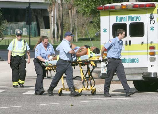 Joe Burbankn/<br>Orlando Sentinel, AP<br> Emergency workers transport a victim from a shooting in downtown Orlando on Friday. Police are searching for a gunman who injured at least eight people at a downtown office building. Orange County Sheriff's Spokesman Jim Solomons says his department is backing up Orlando police and they're still looking for an armed man wearing a light blue polo shirt and jeans.