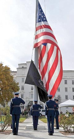 Matt Hinshaw/The Daily Courier<p> Members of the Embry-Riddle Aeronautical University Air Force ROTC color guard raise the American Flag and POW MIA Flag.