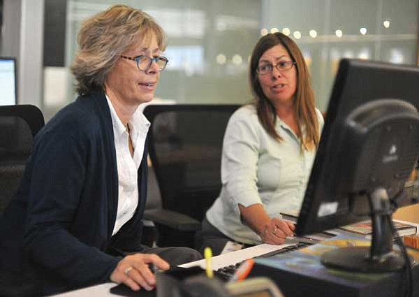 Les Stukenberg/The Daily Courier<br> Cindy Corcoran, left, from the Town of Prescott Valley Legal Department, looks up something on the library's computer system, while Reference Librarian Connie Amenta looks on. Corcoran works at the library five hours a week as part of the town's cost-cutting measures to use employees from other departments to help staff the library.