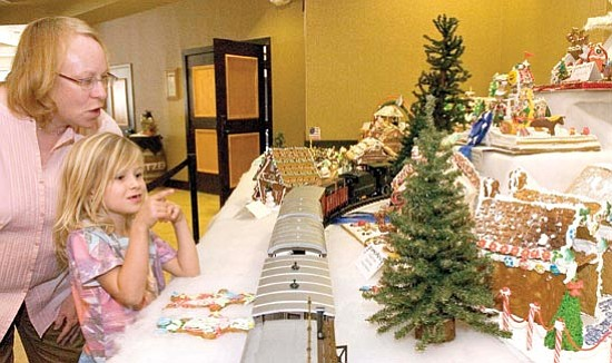 Matt Hinshaw/The Daily Courier<p> Ashlyn Cumming, 6, and her Big Sister Beth Kryskalla of Big Brothers Big Sisters check out the gingerbread village at the Prescott Resort in December 2008.