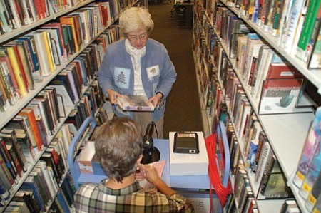 Cindy Barks/The Daily Courier<p> Library volunteers Sharon Phelps, foreground, and Beth Orth work to attach Radio Frequency Identification tags to books in the Prescott Public Library's fiction section. The tags are a preliminary step toward a new security system that library officials hope to implement in coming months.