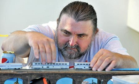 Matt Hinshaw/<br>The Daily Courier<br>Larry Davis assembles an Amtrack model train Tuesday afternoon at the Prescott Valley Civic Center. Davis has been interested in model trains since he was 8 years old.