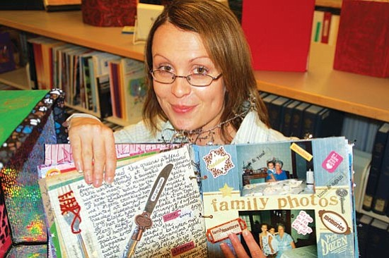 Bruce Colbert/The Daily Courier<p> Yavapai College student Julie Wilson displays her handmade book that contains essays about her family and friends. Students' books are on display at the college's library until Dec. 13.