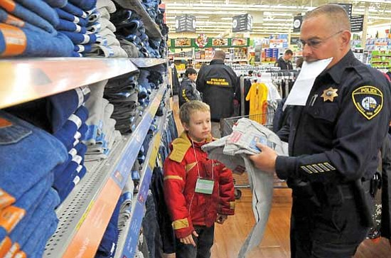 Matt Hinshaw/<br>The Daily Courier<br>Officer Klempner with the Yavapai College Police Department searches for the right pair of cargo pants with Robert, 8, of Prescott during the annual Shop with a Cop event at the Wal-Mart on Gail Gardner in Prescott.