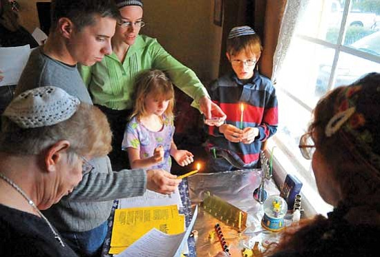 Matt Hinshaw/<br>The Daily Courier<br>From right background to foreground, P.J. Zack, Mirah Zack, hostess Eve Zack, Kevin Holbrook, Ellie Goldberg and Adele Plotkin light their Menorahs late Friday afternoon in Prescott to celebrate the beginning of the Jewish holiday of Hanukkah.