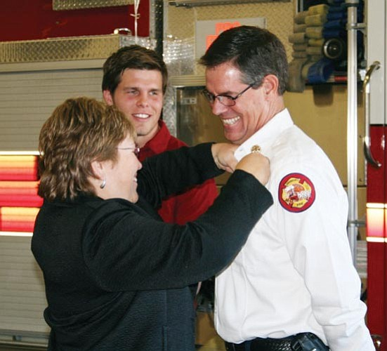 Courtesy photo<p> Prescott Fire Department Chief Bruce Martinez smiles as his wife Brenda Martinez pins him as fire chief Tuesday while his son Mitch Martinez looks on.