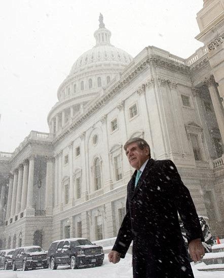 Harry Hamburg/<br>The Associated Press<br> Sen. Ben Nelson, D-Neb., walks in the snow outside the U.S. Capitol Saturday following his agreement to support the health care legislation now pending on Capitol Hill.