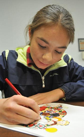 Les Stukenberg/<br>The Daily Courier<br>Shalom Eis, a 13-year-old graphic artist who is the youngest client of the Small Business Development Center at Yavapai College, works on a drawing.