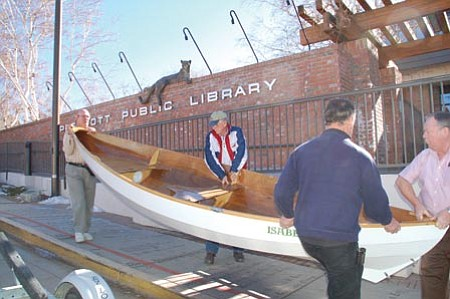 """Bruce Colbert/The Daily Courier<br> Prescott Sailing Club members, from left, Rod Moyer, Jack Seggie, Gary Worob and Dale Carrere carry Seggie's handmade sailboat, the """"Isabella,"""" into the Prescott Public Library Sunday. The boat - along with sailing gear, photographs and model ships - is on display through the end of January."""