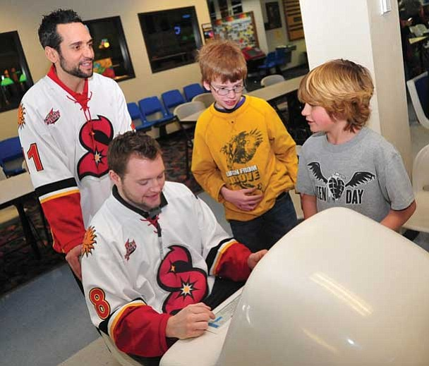 "Les Stukenberg/The Daily Courier<br> Arizona Sundogs Steve Potvin and Kyle Hood come up with nicknames for PJ Zack and Jackson Rauch as five Sundogs bowled with some ""littles"" from Yavapai Big Brothers/Big Sisters on Wednesday afternoon at Antelope Lanes in Prescott Valley."