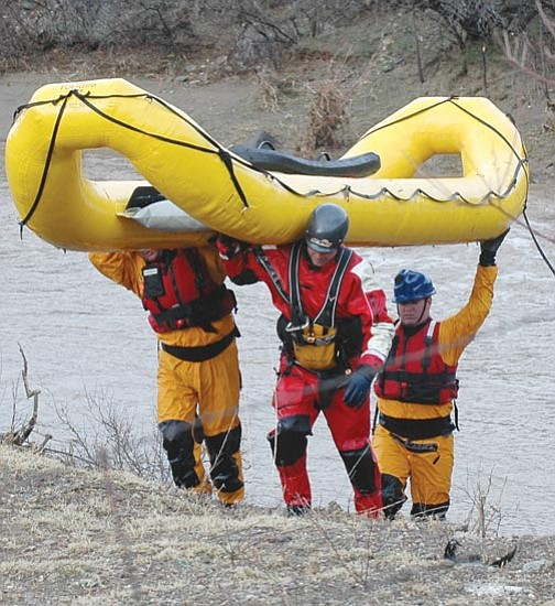 Heidi Dahms Foster/Courtesy<br> Central Yavapai Fire swift water rescue team members haul their boat out of the water Friday afternoon at the Agua Fria Bridge at Interstate 17. The rescuers spent the afternoon searching for a 6-year-old boy lost in flood waters Thursday night.