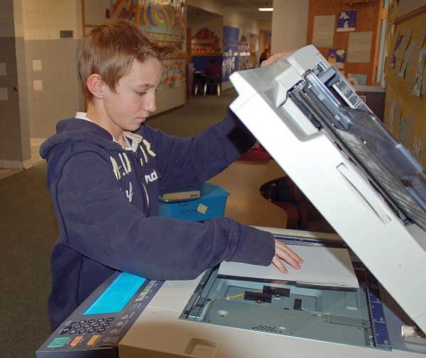 The Daily Courier<br> Seventh-grader Zane Galpin makes copies for third-grade teacher Suzanne Yoder, as part of his teaching assistant duties.