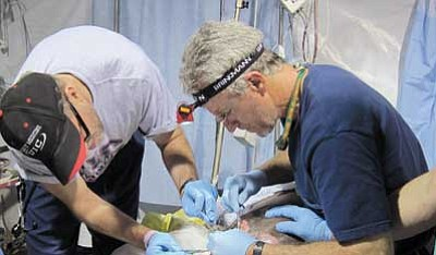 Courtesy photo<br/>Surgeon Bill Ennis, a wound-care specialist from Chicago, left, and Prescott general surgeon Thomas W. Rusing, right, remove dead tissue from a large wound a victim suffered in the Jan. 12 earthquake that struck Haiti.