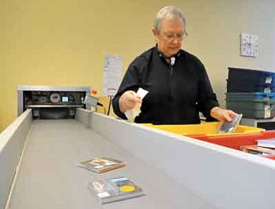 Matt Hinshaw/The Daily Courier<br/><br/>Jan Christman sorts through books, CDs and DVDs at the Prescott Valley Public Library Thursday morning. Christman has been volunteering at the library since 1999 and typically works 30 hours a week.<br/><br/>