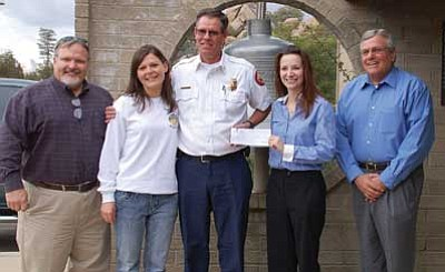 Lisa Irish/The Daily Courier<br/>From left to right, Bob McKeever, director of sales for Fred Nackard Wholesale Beverage and Kristi Gagnon, fire inspector for Prescott Fire Department, look on as  Prescott Fire Chief Bruce Martinez accepts a check from Laura Davis, marketing manager for Pepsi, and John Vandevier, director of marketing for Pepsi.
