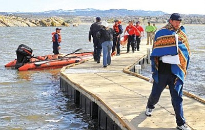 Matt Hinshaw/The Daily Courier<br/>An unidentified 35-year-old man walks to shore bundled up in towels and blankets after his single-person kayak turned over in Willow Lake Thursday afternoon.  <br/>
