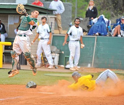 Matt Hinshaw/The Daily Courier<br /><br /><!-- 1upcrlf2 -->Yavapai College catcher Aaron Fujiki, left, goes up high for a overthrown ball versus Central Arizona.