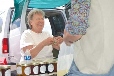 Doug Cook/The Daily Courier<br>Ernie Riley of Phoenix-based Cotton Country Jams sells her gourmet jams to customers at the Prescott Farmers Market Saturday morning on Yavapai College's main parking lot.