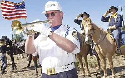 Courier file<br> John Stevens, left, 2nd Asst. Bugler with the American Legion Ernest A. Love Post 6 Color Guard, plays the trumpet as members of the Camp Verde Cavalry salute the American and Arizona flag at the 2009 Memorial Day service at the Citizens Cemetery in Prescott.