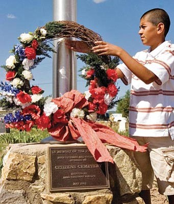 Matt Hinshaw/The Daily Courier<br> Justin Castro, a third-generation Lincoln School graduate, places a wreath during the 2009 Memorial Day services at Citizens Cemetery in Prescott.