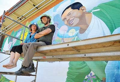 "Matt Hinshaw/The Daily Courier <br>Mural Mice Pamela J. Smith, co-artist, and R.E. Wall, co-artist and project director, sit on the scaffolding in front of the Miller Valley School mural titled "" Go on Green"" Wednesday afternoon in Prescott. In the next few days the artists will be making adjustments to the new mural."