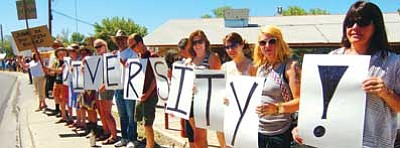 """Les Stukenberg/The Daily Courier<br> Many of the members of the public held up signs during a rally Saturday in support of the mural and """"DIVERSITY."""""""