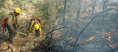Les Stukenberg/The Daily Courier<br> Crew members from Prescott National Forest's Engine 32 clean up the fire line at the Creek Fire, one-half mile east of Ponderosa Park on the Wolf Creek Cutoff in the Prescott National Forest on Wednesday.