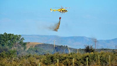 Matt Hinshaw/The Daily Courier<br> A helicopter drops a bucket of water on a brush fire near Mayer Friday afternoon.