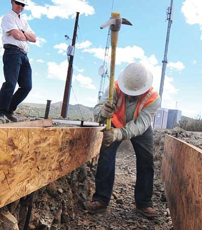 Les Stukenberg, file/The Daily Courier<br> Lorenzo Llamas of RGG uses a pick this past May to break up rocks along what will be the footer of the new 1.33-million-gallon water tank atop Indian Hill in Prescott.