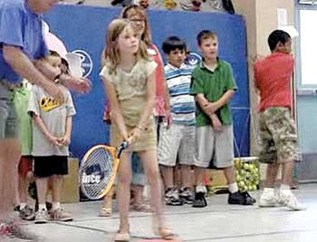 Paula Rhoden, image from video/The Daily Courier<br> Children at Kids & Company take turns at tennis lessons recently.
