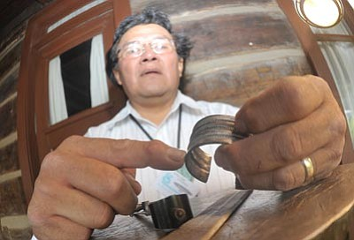 Les Stukenberg/The Daily Courier<br>Ernie Lister, a Navajo, shows the differences in silversmithing during a demonstration. The market continues today.