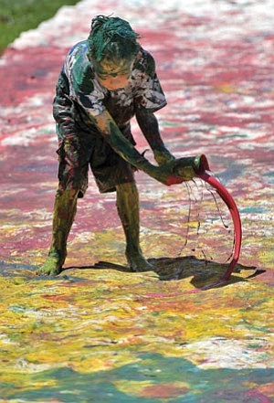 "Matt Hinshaw, file/The Daily Courier<br> Salem Soma, 7, sloshes paint on a canvas for the ""Plunge for the World Record"" painting during the 2009 World Arts Festival in Prescott Valley."