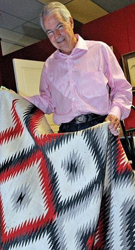Brett Soldwedel/The Daily Courier<br> Jeff Ogg, owner of Ogg's Hogan in downtown Prescott, holds a rug that will be available at the Smoki Museum's Indian Art and Rug Auction on Saturday.