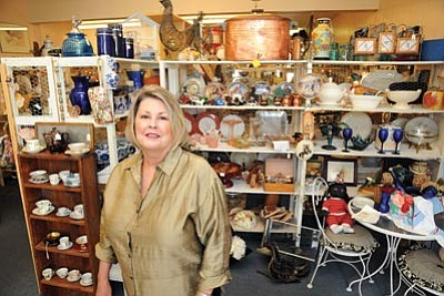 Brett Soldwedel/ The Daily Courier<br> Muriel Kropp, owner of Sweet Violet's in Prescott Valley, poses in front of a vast array of collectibles and antiques in her store Thursday.