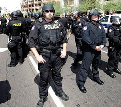 Phoenix police block the street Thursday in Phoenix while protesters rally against Arizona's new immigration law, SB 1070. <i>(Matt York/The Associated Press)</i>